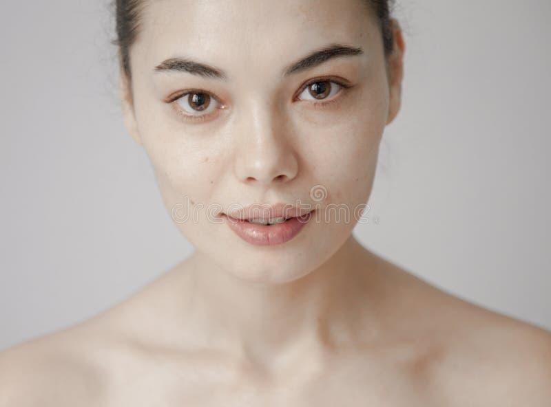 Schöner Gesichtsabschluß der gesunden Hautfrau oben über grauem Hintergrund stockfoto