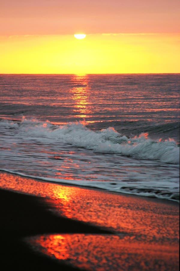 Schöner goldener Sonnenaufgang, wie vom sandigen Strand in Marbella gesehen stockfoto
