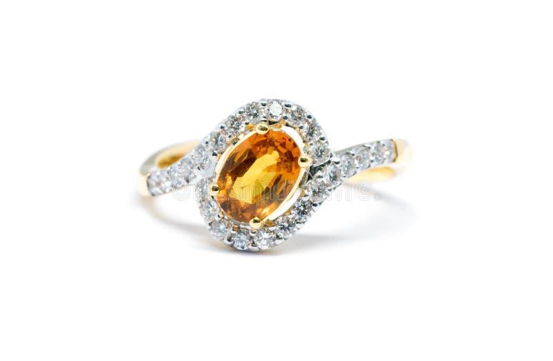 Schöner Goldring mit dem Diamanten und gelbem Saphir lokalisiert stockbilder
