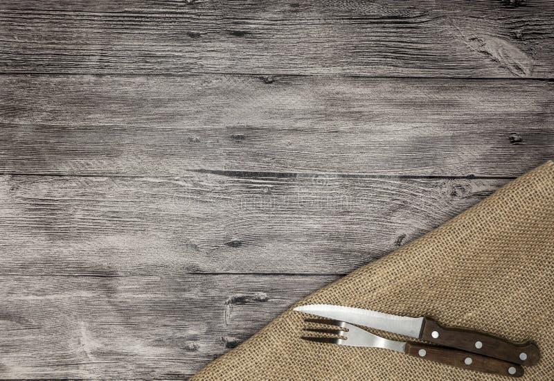 Schöner hölzerner Hintergrund mit Serviettenmesser und -gabel Feiner Hintergrund für das Menü von Restaurants und von Cafés lizenzfreies stockbild