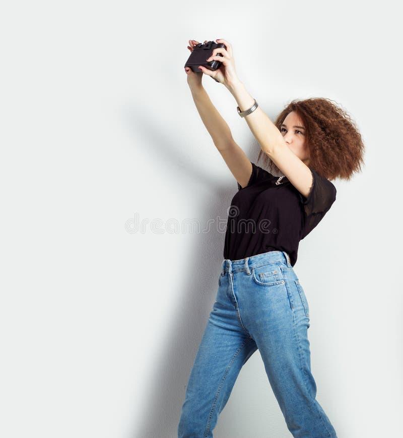 Schöner Hippie des jungen Mädchens macht Fotos, schießt das selfe und macht Fotos von auf Kamera in den Jeans und in einem schwar stockfoto