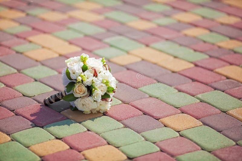Schöner Hochzeitsblumenstrauß auf bunten Pflastersteinen stockfotografie
