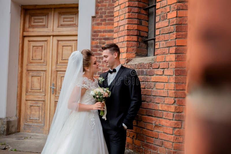 Schöner Hochzeitspaarehemann im Anzug und in der Frau im Hochzeitskleid, das nahe der Wand aufwirft lizenzfreie stockbilder