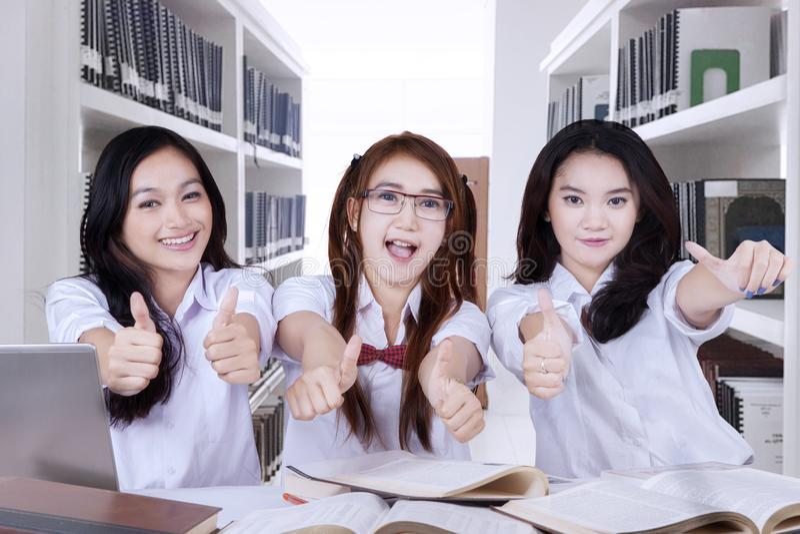 Schöner hoher Schüler, der sich Daumen zeigt lizenzfreies stockfoto