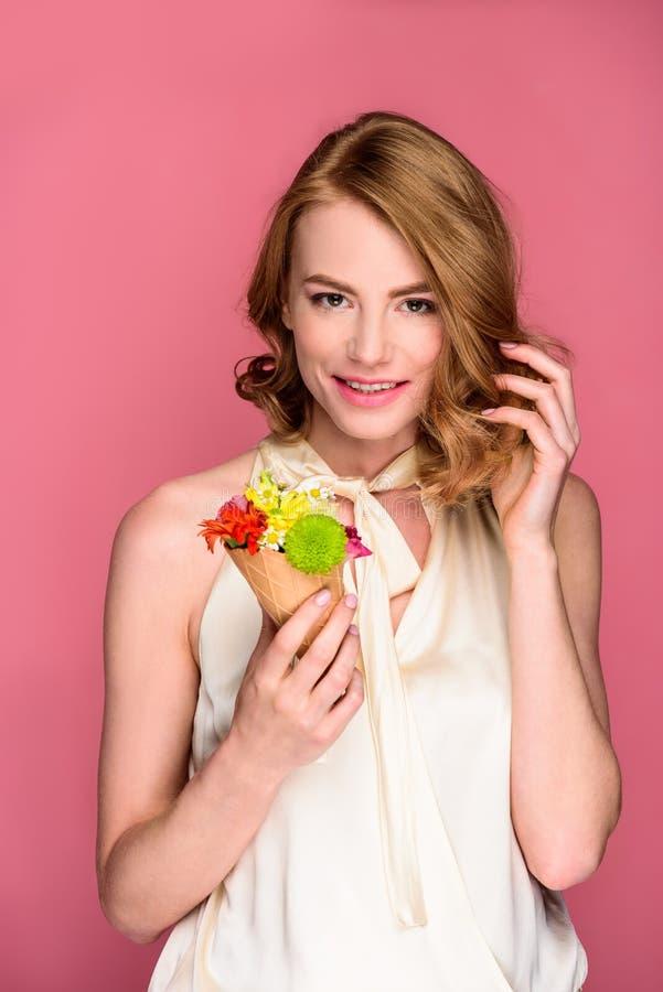 schöner Holdingoblatenkegel der jungen Frau mit Blumen und Lächeln an der Kamera lizenzfreies stockbild