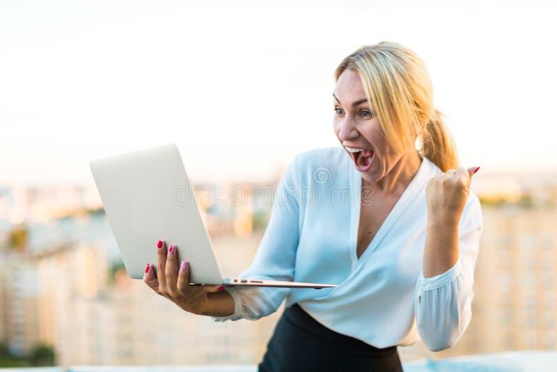 Schöner intelligenter Geschäftsdamenstand auf dem Dach mit Laptop in h stockfotografie