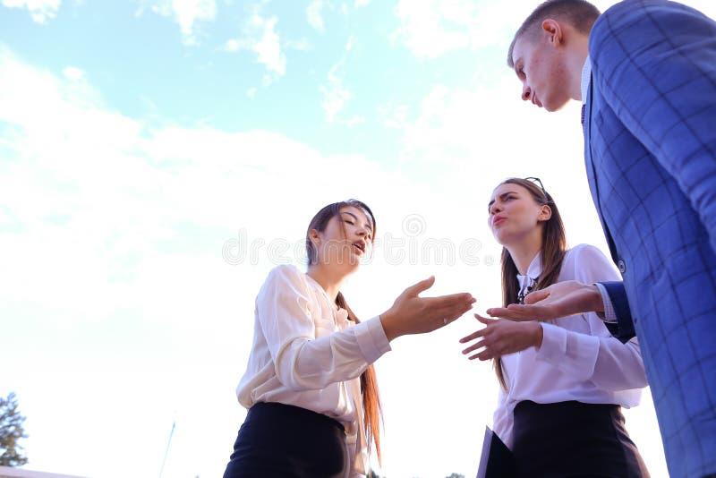 Schöner intelligenter junger Geschäftsmann drei, der, Hände rüttelnd spricht, stockfotos