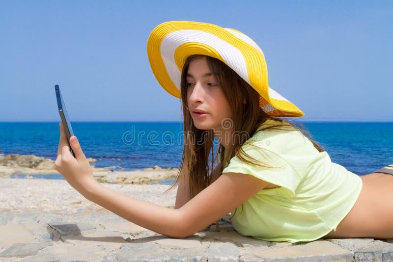Schöner Jugendbrunette, der eine Tablette durch verwendet lizenzfreie stockfotos