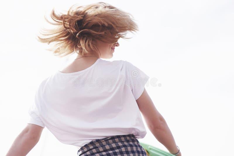 Schöner jugendlich weiblicher Schlittschuhläufer, der auf Rampe am Rochenpark sitzt Konzept von städtischen Tätigkeiten des Somme lizenzfreie stockfotografie