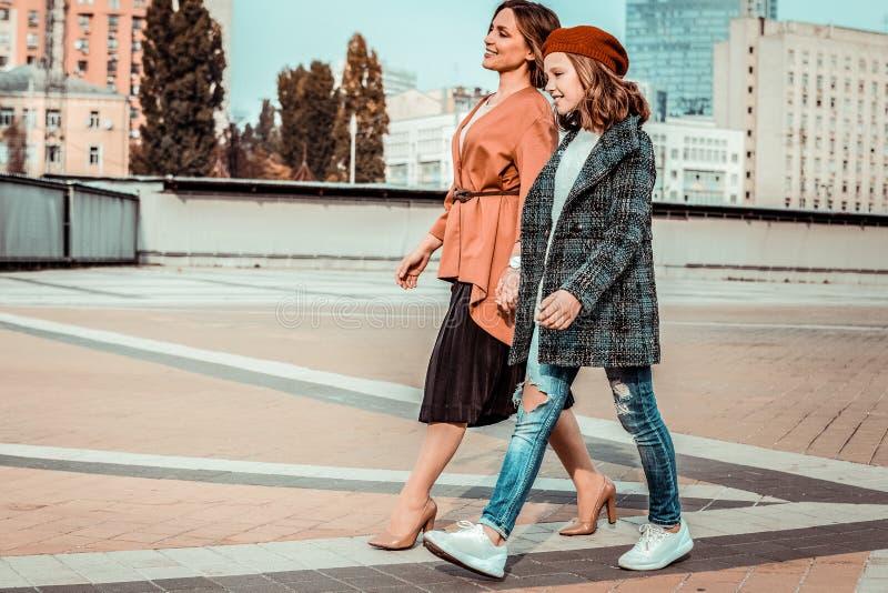 Schöner Jugendlicher, der Hand in Hand mit Mutter geht stockfoto