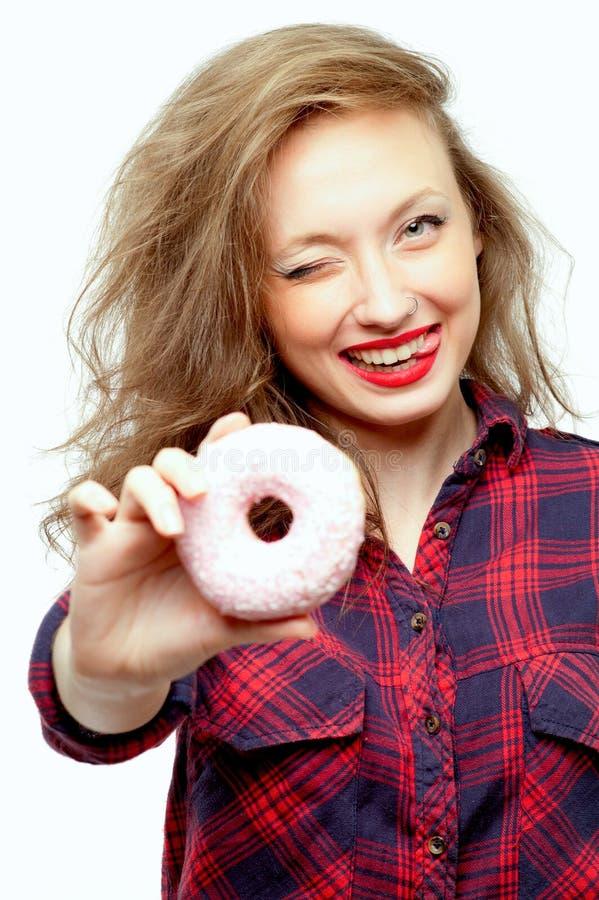 Schöner Jugendlicher mit einem rosa Donut lizenzfreies stockfoto