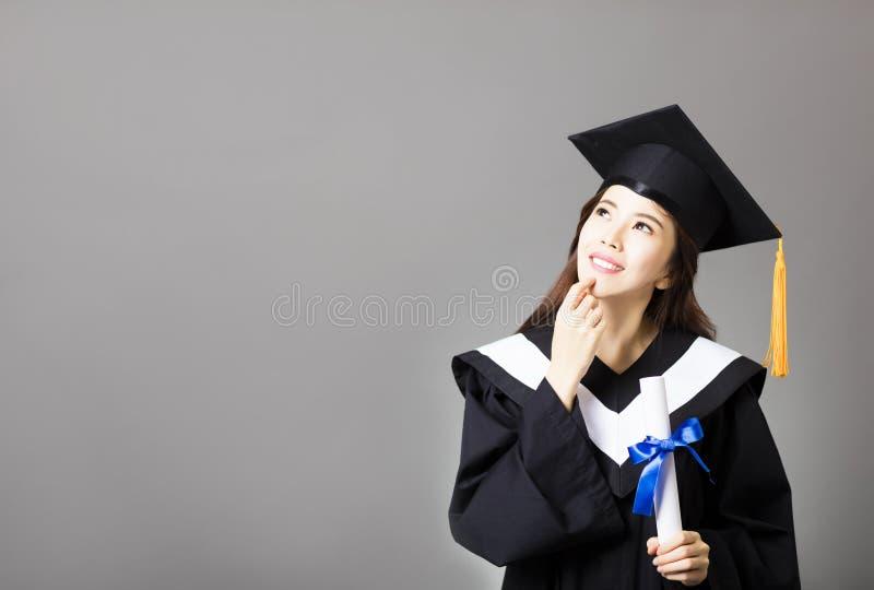 Schöner Jungakademiker, der Diplom und das Denken hält stockfoto