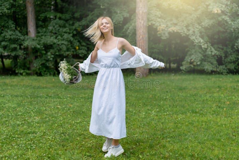 Schöner junge Frauen-Freienholdingkorb mit Gänseblümchen Genie?en Sie Natur Gesundes l?chelndes M?dchen im gr?nen Gras lizenzfreies stockfoto