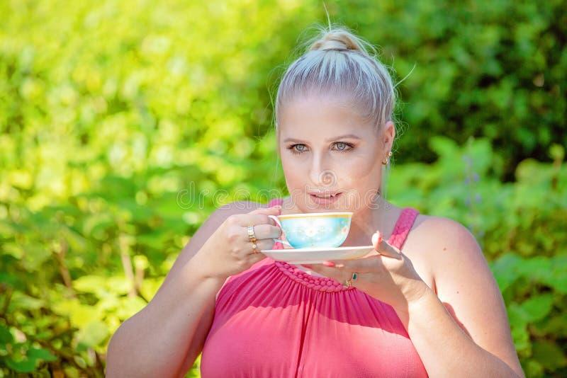 Schöner junge Frauen-nippender Tee in The Sun lizenzfreies stockfoto