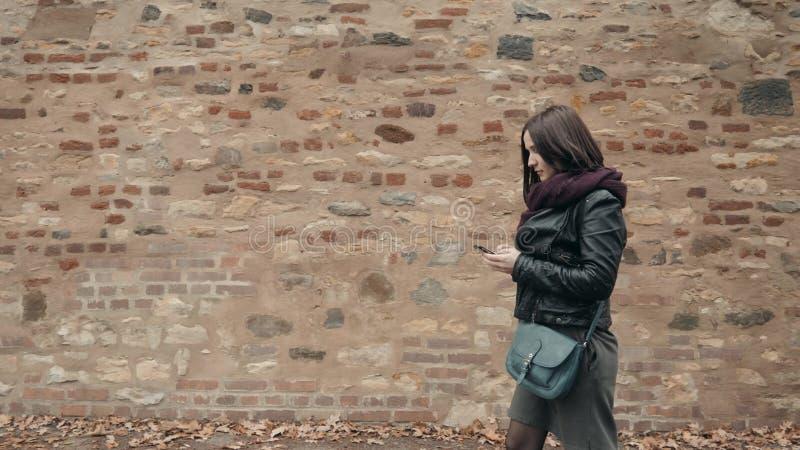 Schöner junge Frauen-Tourist, der ihr Smartphone, reisendes Konzept geht und verwendet lizenzfreies stockbild