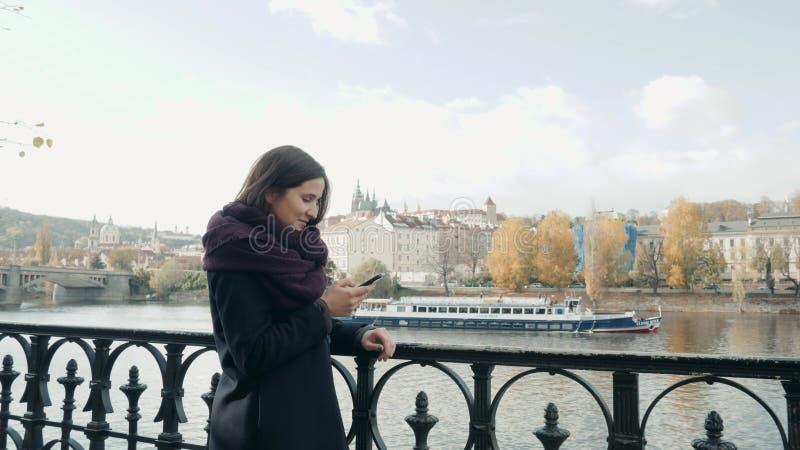 Schöner junge Frauen-Tourist in Prag unter Verwendung ihres Smartphones, reisendes Konzept lizenzfreies stockfoto