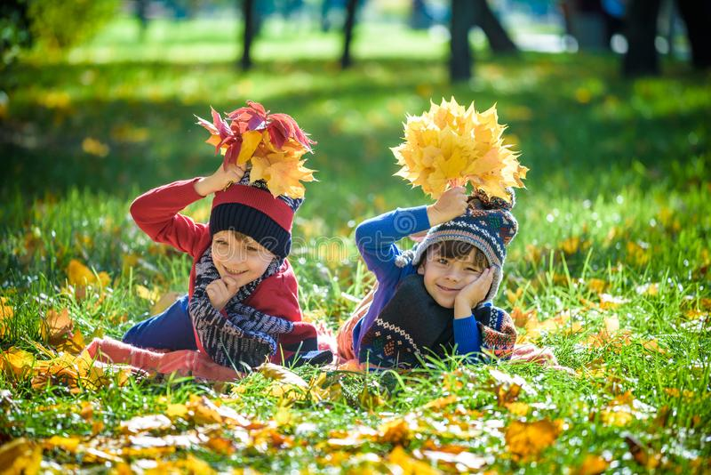 Schöner Junge, kleines Kind, das mit vielem gelben Herbstlaub im Park legt Scherzen Sie den Jungen, der Spaß an sonnigem warmem O stockbild