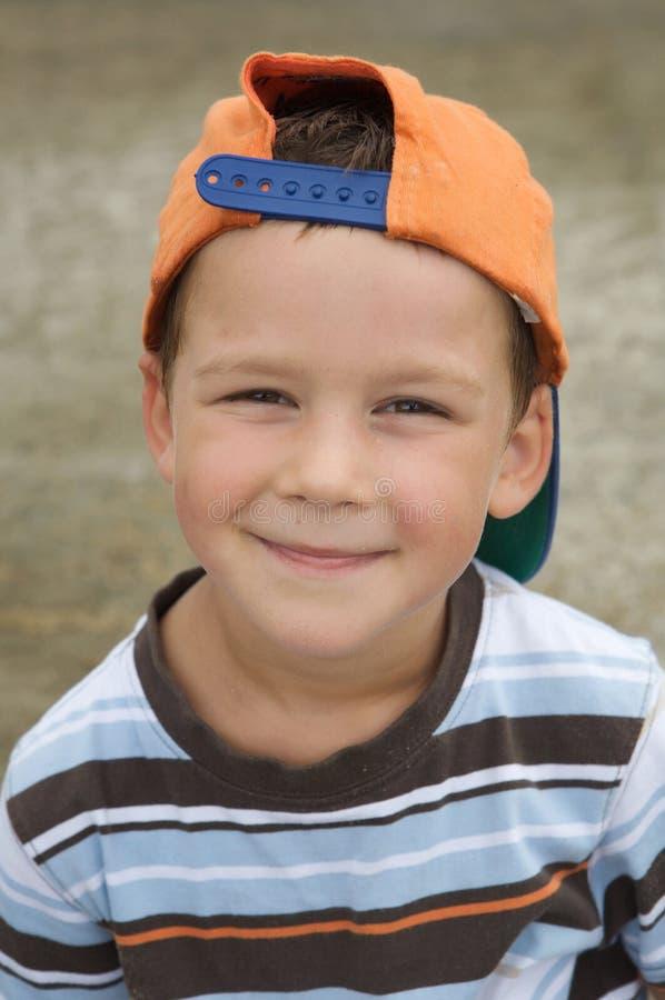Schöner Junge mit dem Schutzkappenlächeln lizenzfreies stockbild