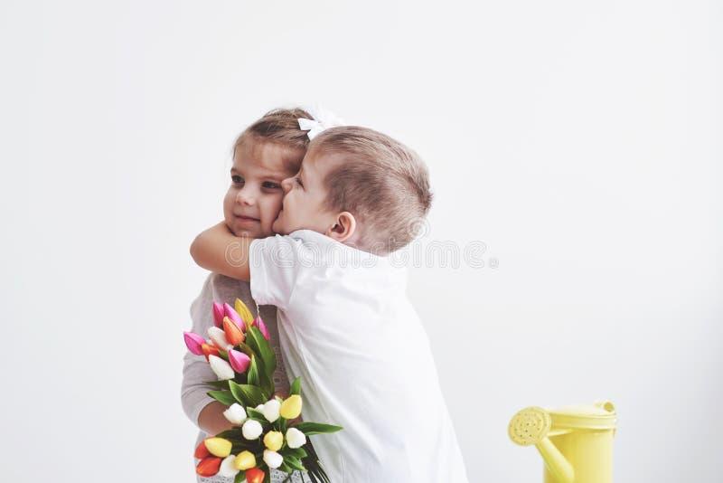 Schöner Junge und Mädchen mit Tulpen mit Umarmung Muttertag am 8. März alles Gute zum Geburtstag lizenzfreies stockbild