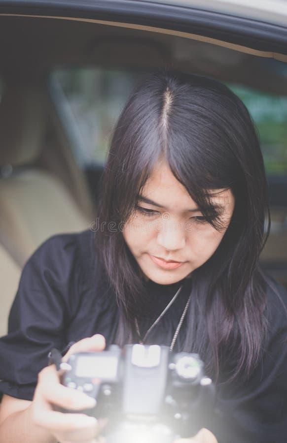 Schöner junger asiatischer Frauenphotograph, der Fotos überprüft und Digitalkamera hält lizenzfreies stockfoto