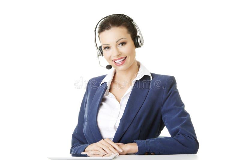 Schöner junger Aufrufmitte Assistent am Schreibtisch stockfotografie