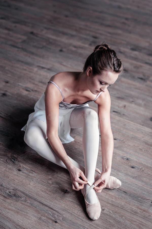 Schöner junger Balletttänzer, der auf dem Boden sitzt stockbild