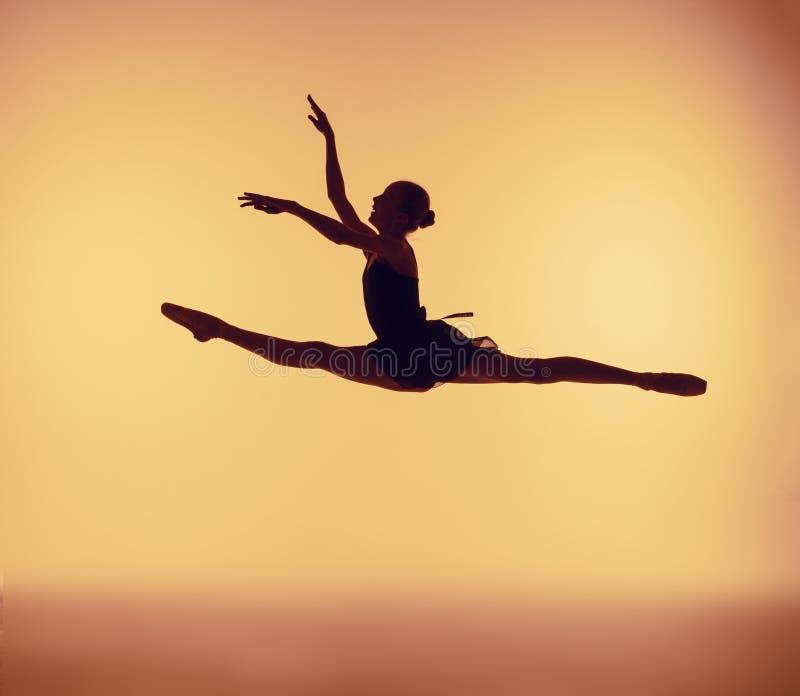 Schöner junger Balletttänzer, der auf einen orange Hintergrund springt stockfoto
