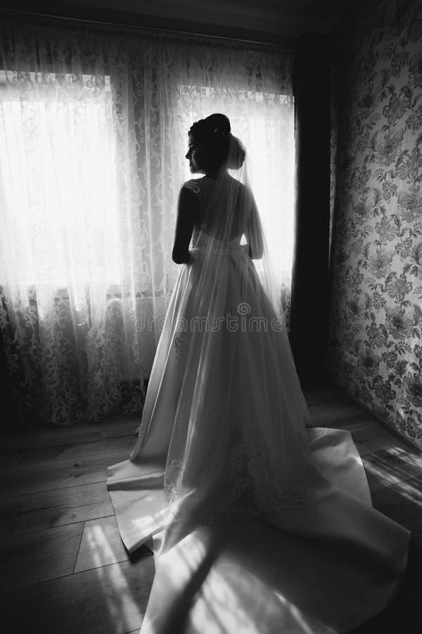 Schöner junger Brautstand vor dem Fenster in ihrem Raum Rebecca 6 stockbild