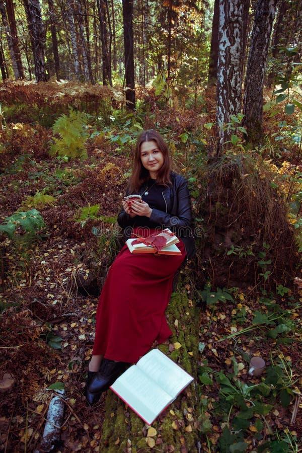 Schöner junger Brunette, der auf gefallenen Herbstlaub in einem Park, ein Buch lesend sitzt stockfoto