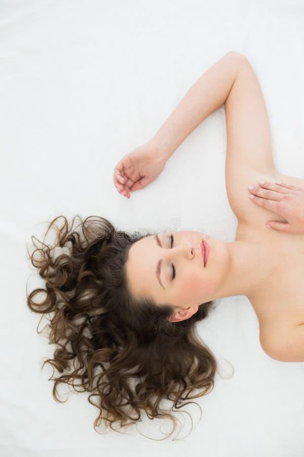 Schöner junger Brunette, der im Bett schläft stockfoto