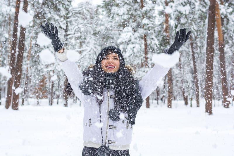 Schöner junger Brunette, der Spaß im Winterwald hat stockbilder