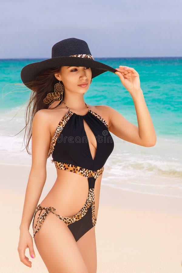 Schöner junger Brunette in einem Strohhut und in einem schwarzen Badeanzug lizenzfreies stockbild