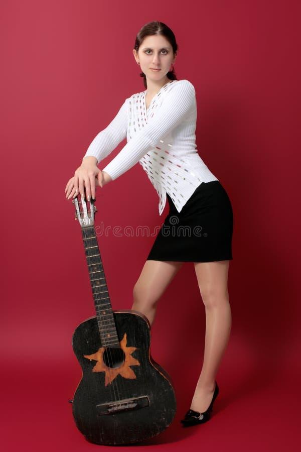 Schöner junger Brunette mit einer schwarzen Gitarre lizenzfreie stockbilder