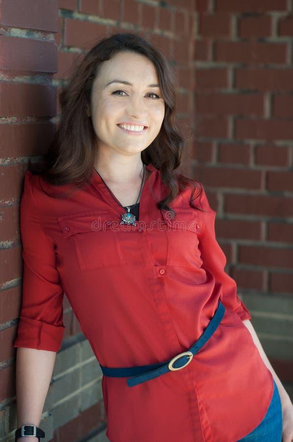 Schöner junger Brunette nahe Wand des roten Backsteins - 3 lizenzfreies stockbild