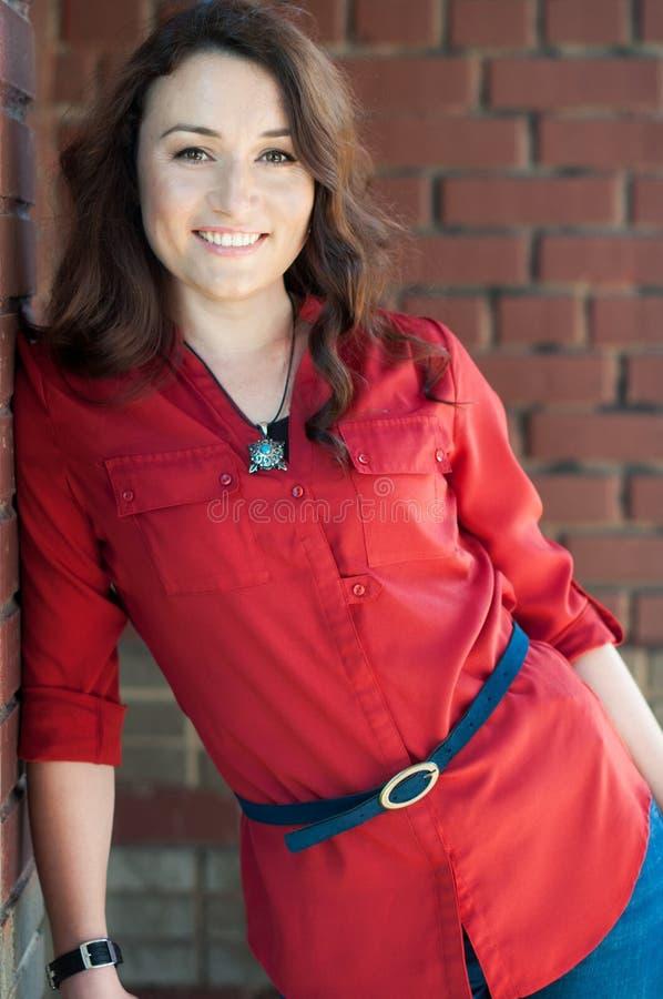 Schöner junger Brunette nahe Wand des roten Backsteins - 2 lizenzfreie stockbilder