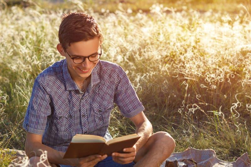 Schöner junger glücklicher Kerl mit Gläsern ein Buch an einem sonnigen Tag draußen lesend stockfotografie