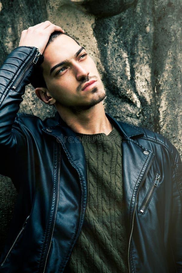 Schöner junger kühler Mann mit der Hand auf Kopf lizenzfreies stockfoto