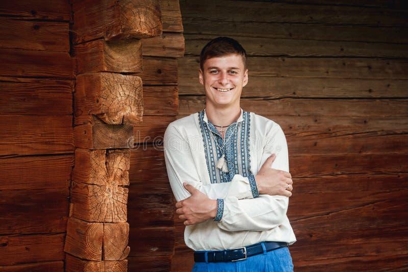 Schöner junger Kerl in einem gestickten Hemd auf dem Hintergrund eines Holzhauses stockbilder