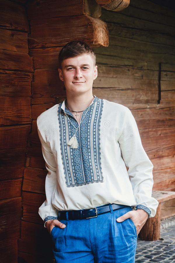 Schöner junger Kerl in einem gestickten Hemd auf dem Hintergrund eines Holzhauses lizenzfreies stockbild