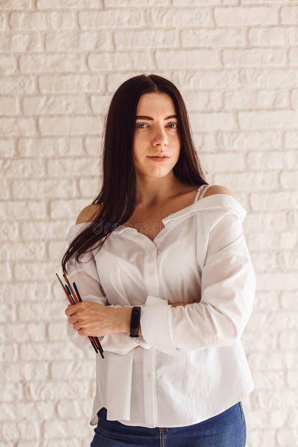 Schöner junger Kosmetikerfrauen-Holdingsatz von bilden Bürsten lizenzfreie stockfotografie
