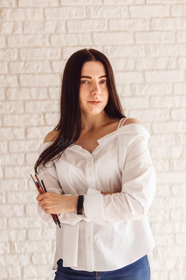 Schöner junger Kosmetikerfrauen-Holdingsatz von bilden Bürsten stockfoto