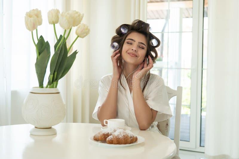 Schöner junger lächelnder Brunette in den Haarlockenwicklern hörend Musik beim Frühstücken in der hellen Küche lizenzfreie stockfotos