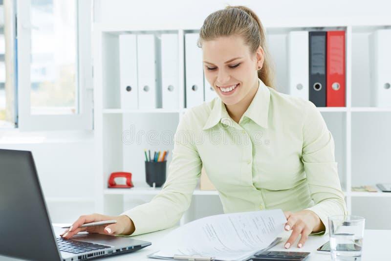 Schöner junger lächelnder Sekretär, der mit den Papieren sitzen im Büro arbeitet lizenzfreie stockfotografie