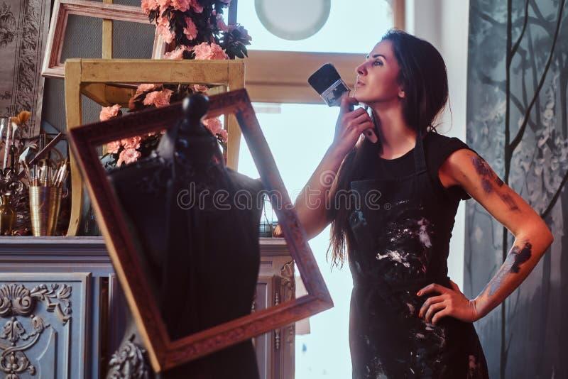 Schöner junger Maler wirft nahe Mannequin whith Bürste auf stockbilder