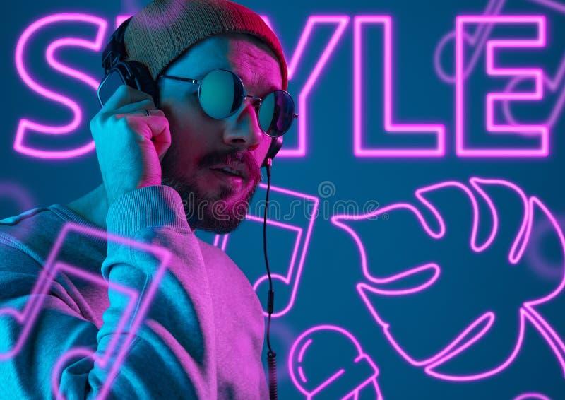 Schöner junger Mann auf Studiohintergrund im Neonlicht stockfotografie