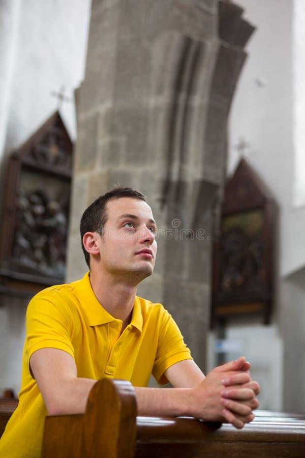 Schöner junger Mann beten stockfotos