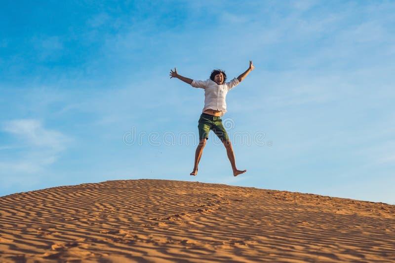 Schöner junger Mann, der barfuß auf Sand beim Wüstengenießen springt lizenzfreie stockfotos