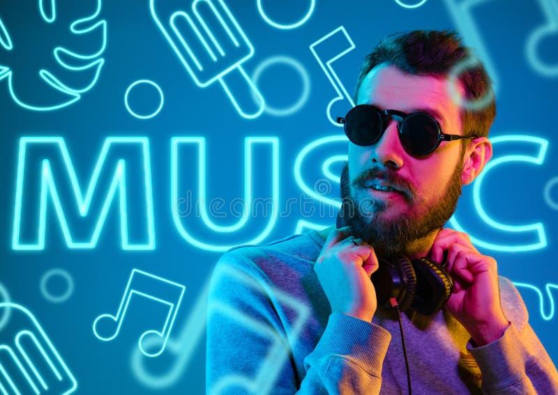 Schöner junger Mann lokalisiert auf Studiohintergrund im Neonlicht stockfoto