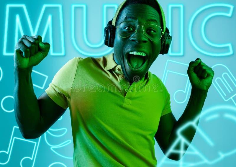 Schöner junger Mann lokalisiert auf Studiohintergrund im Neonlicht stockbilder