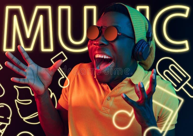 Schöner junger Mann lokalisiert auf Studiohintergrund im Neonlicht lizenzfreies stockbild